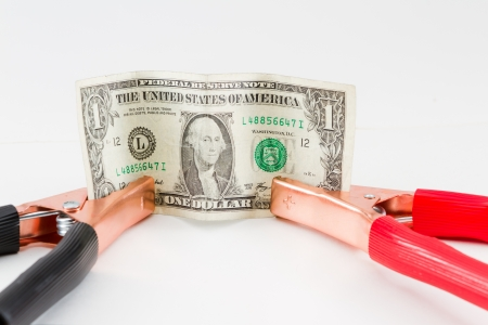 fiscal cliff: booster cables attached to a american dollar bill on a white background Stock Photo