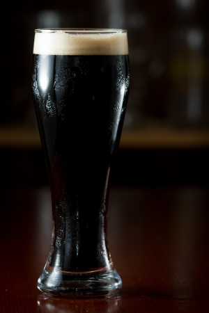 cerveza negra: stout irlandesa sirve en un vaso en un bar oscuro