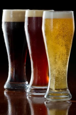 pilsner: dark, red and light beer served on a dark bar