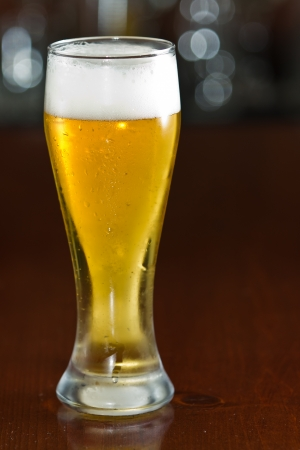 pilsner beer glass: single beer served in a bar with an out of focus background