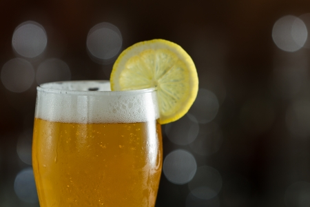 hour glasses: single beer served in a bar with an out of focus background