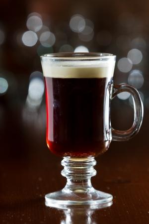 close-up van een Ierse koffie opgeslagen op een donkere bar met een float van slagroom