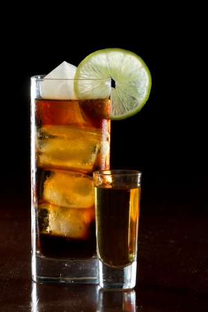 cuba libre, rum and cola cocktail served in a tall glass with a lime garnish and a shot of rum on the side