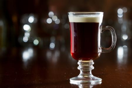 close-up van een Ierse koffie opgeslagen op een donkere bar met een vlotter slagroom