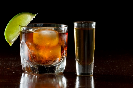 cuba libre, rum and cola cocktail served in a short glass with a lime garnish and a shot of rum on the side