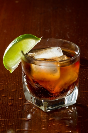 cuba libre, rum and cola cocktail served in a short glass with a lime garnish