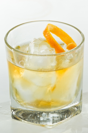 whiskey served on ice garnished with an orange twist isolated on a white background photo
