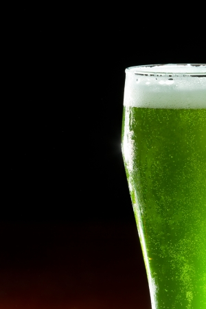 green beer isolated on a wooden bar, classic St. Patricks day beverage photo