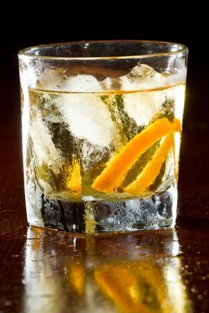 whisky geserveerd op ijs gegarneerd met een oranje tintje geserveerd op een houten balk