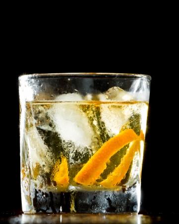 whiskey served on ice garnished with an orange twist served on a wooden bar Reklamní fotografie