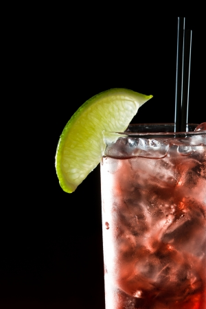 classic cocktail, cape cod served in a glass on a dark bar garnished with a lime photo