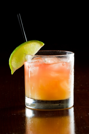 cocktail drinks: classic cocktail, madras, vodka cranberry and orange juice served in a glass on a dark bar