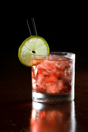 classic cocktail, cape cod served in a glass on a dark bar garnished with a lime Foto de archivo