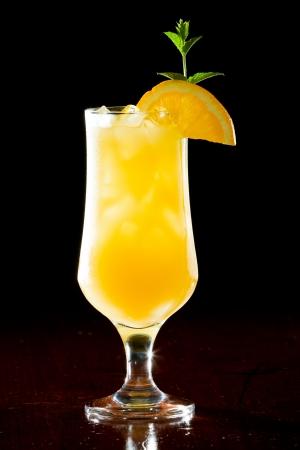alcohol screwdriver: screwdriver, fresh orange juice with vodka served in a stem glass on a dark bar