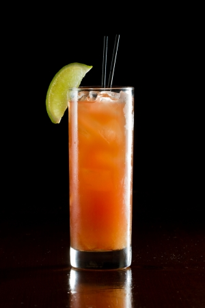 classic cocktail, madras, vodka cranberry and orange juice served in a glass on a dark bar photo