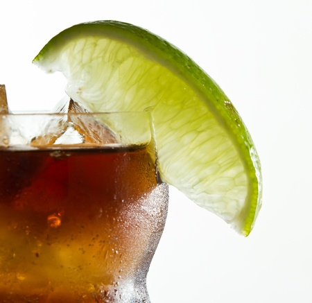 lime garnish on a rum and cola drink isolated on a white background Banco de Imagens