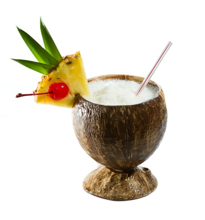 alcoholic drink: closeup of a tropical coconut drink garnished with a pineapple slice with leaves and a cherry