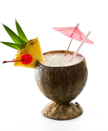 closeup of a tropical coconut drink garnished with a pineapple slice with leaves and a cherry photo