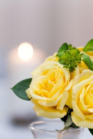 yellow rose: closeup of yellow roses as a centerpiece with a candle on the background