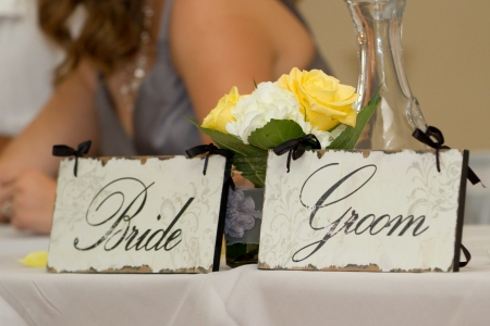 bride and groom place holders on a table with flowers behind it