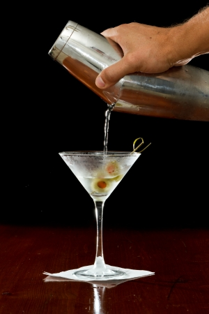 hand pouring a martini into  a chilled glass over a black background photo