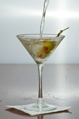 dirty vodka martini splashing into a cocktail glass with green olives photo