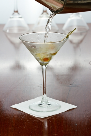 pouring a martini into  a chilled glass over a black background photo