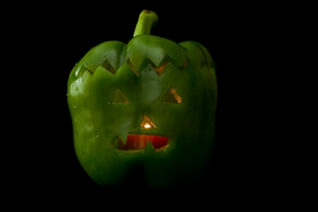 hand carved green bell pepper for halloween set on a dark background photo