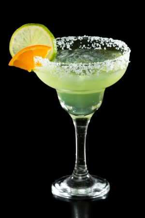 green margarita isolated on a black background served with a thick salt rim and a lime and orange on the rim photo