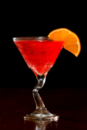 red cocktail isolated on a dark bar garnished with an orange slice