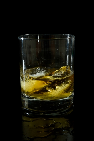 drunks: glass of whiskey on the rocks isolated on a black background