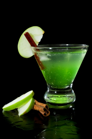 closeup of a green apple martini isolated on a black background garnished with an apple slice and a cinnamon stick Stock Photo - 22495133