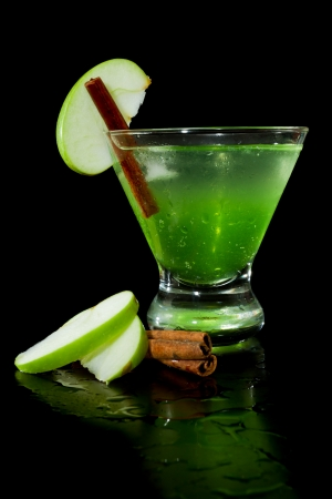 closeup of a green apple martini isolated on a black background garnished with an apple slice and a cinnamon stick Stock Photo - 22495623
