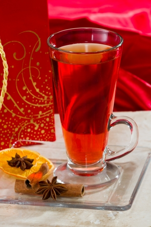 christmas morning: christmas morning tea served in a tall clear glass with spices and a red table cloth