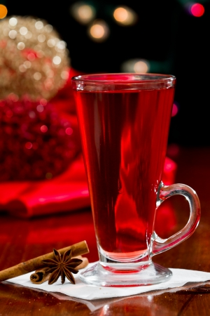 christmas morning tea served in a tall clear glass with spices and a red table cloth photo