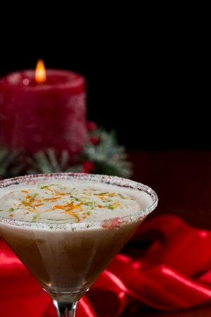 holiday martini with a sugar rim and lime and orange zest on top served on a table with decorations 写真素材
