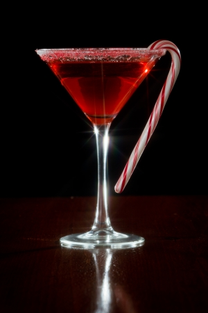 Holiday martini served on a dark background with a candy cane garnish, shot with a star filter Foto de archivo