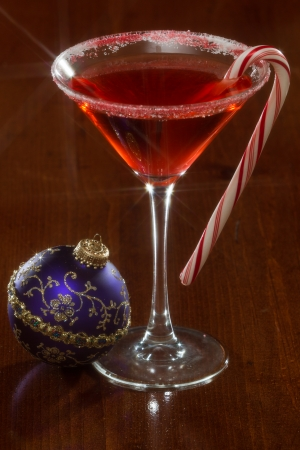 Holiday martini served on a dark background with a candy cane garnish, shot with a star filter photo