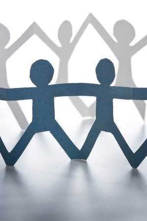 coming together: paper cutout of people. concept of people coming together and working as a team