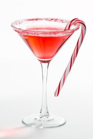 Holiday martini isolated on a white background with a red and white sugar rim