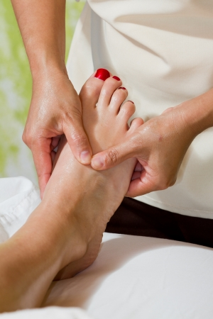 caucasian woman on a tropical vacation receiving a foot massage photo