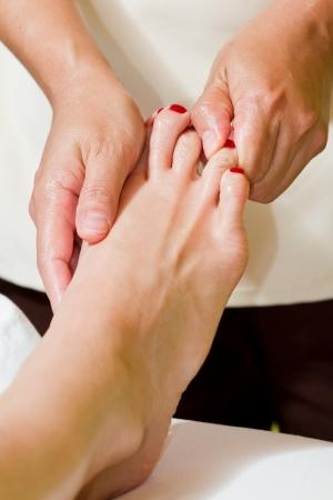 caucasian woman on a tropical vacation receiving a foot massage Фото со стока