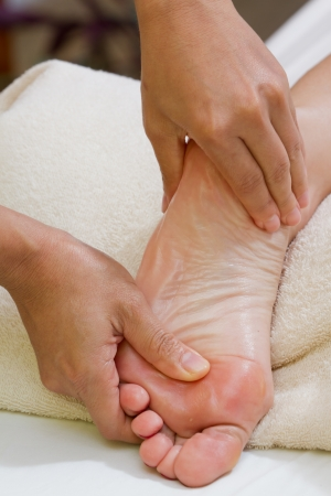 hands giving a foot massage with a white towel on the background photo