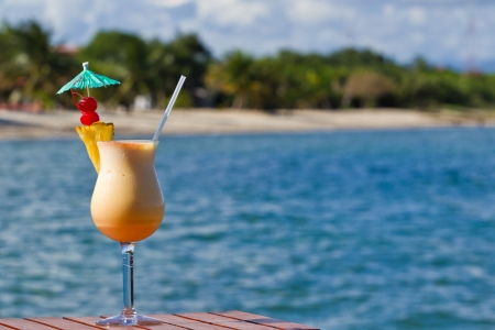colada: pina colada served on the beach garnished with fresh pineapple and cherries
