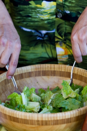 tossing: closeup of hands tossing a salad using forks
