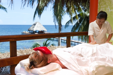 caucasian woman on a tropical vacation receiving a full body massage