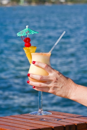 pina colada served on the beach garnished with fresh pineapple and cherries photo