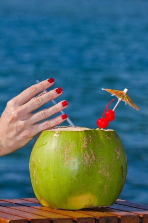 coconut drink served in a green coconut with rum and juices served on the beach of Belize photo
