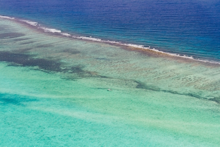 aerial view of the barrier reef of the coast of San Pedro, Belize. with large waves breaking away from the coast photo
