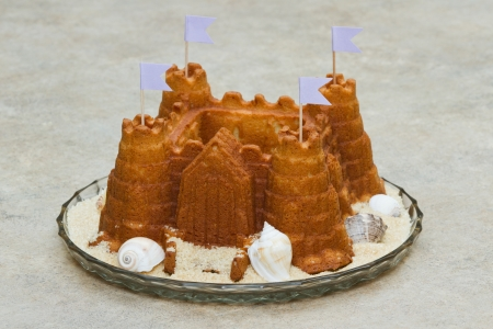 sand mold: fresh baked cake in shape of a castle with sugar and shells on the plate